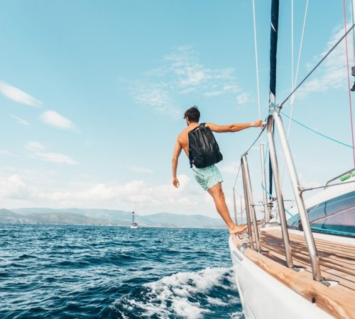 Man wearing backpack standing on side of boat during day